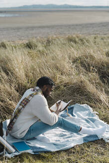 Young man writing in diary while sitting on blanket amidst dried plant at beach - BOYF01840