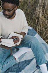 man on the beach writing on his journal. Dublin Ireland - BOYF01846