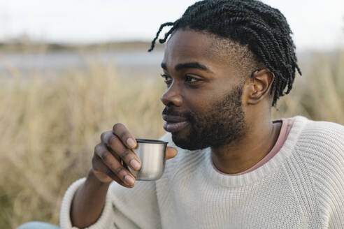 Smiling young man drinking tea while looking away - BOYF01855