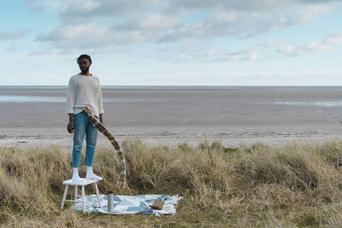 African man looking away while standing on stool at beach - BOYF01864