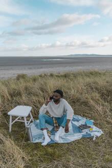 Man on the beach using a mobile phone - BOYF01873