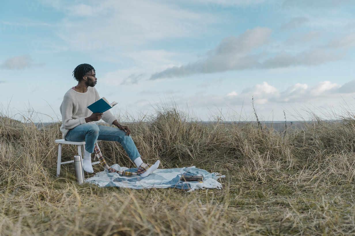 Junger afrikanischer Mann mit Buch schaut weg, während er auf einem Hocker gegen den bewölkten Himmel sitzt - BOYF01879 - Boy/Westend61