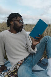 African man in eyeglasses reading book sitting against cloudy sky - BOYF01888