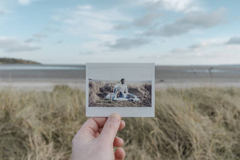 Hand holding instant photography at the beach - BOYF01891