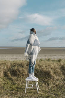 African man wrapped in blanket standing on still at beach against cloudy sky - BOYF01894