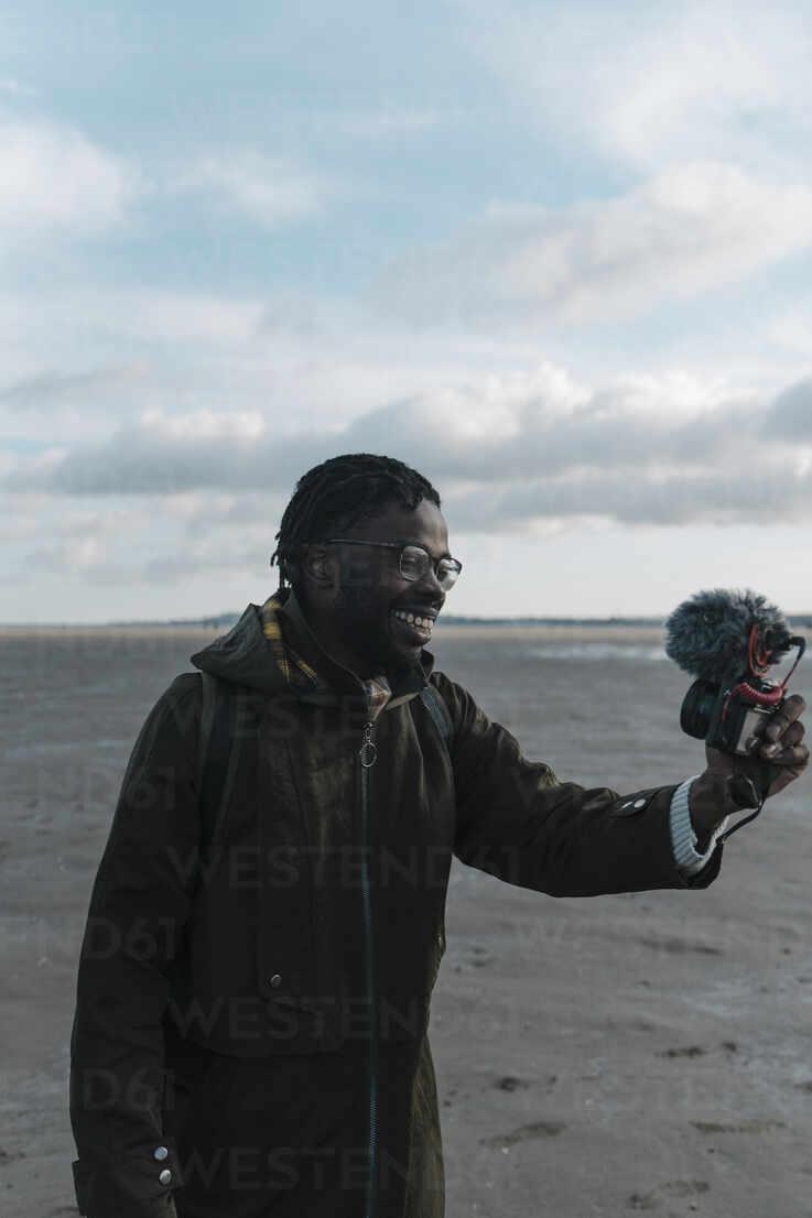 Lächelnde männliche Vlogger Live-Streaming durch Kamera am Strand gegen den Himmel - BOYF01903 - Boy/Westend61