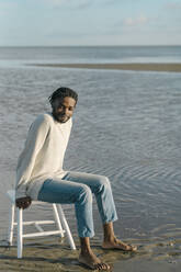 Smiling young man looking away while sitting on white stool at beach during sunset - BOYF01909