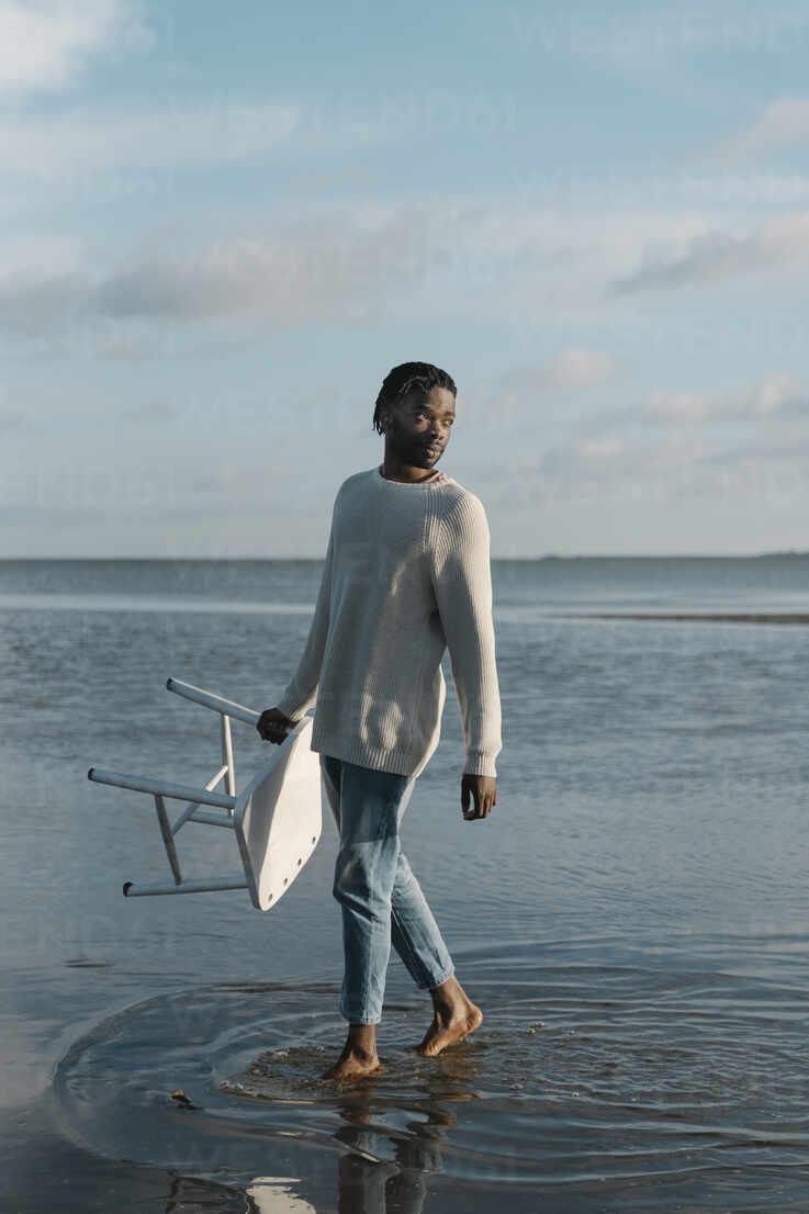 Mann mit weißem Hocker schaut weg, während er am Strand gegen den Himmel läuft - BOYF01915 - Boy/Westend61
