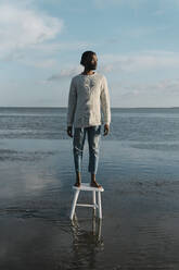 Thoughtful young man looking away while standing on stool at beach during sunset - BOYF01918
