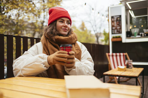Woman with coffee cup looking away while sitting at sidewalk cafe - OYF00315