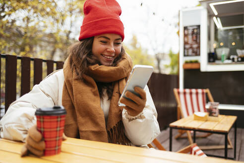 Smiling young woman using mobile phone while sitting at sidewalk cafe - OYF00318