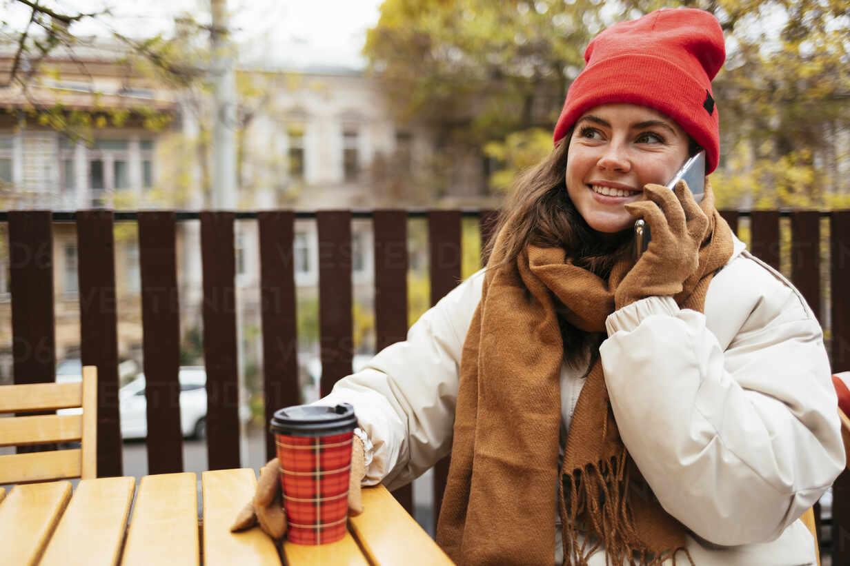Frau in warmer Kleidung spricht am Handy, während sie in einem Straßencafé sitzt - OYF00321 - alev/Westend61