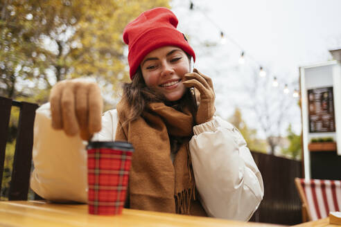 Smiling woman looking at disposable cup while talking on mobile phone sitting at sidewalk cafe - OYF00324