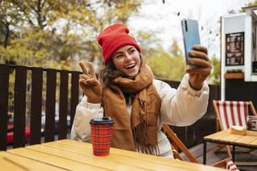 Happy woman gesturing peace sign while taking selfie through mobile phone sitting at sidewalk cafe - OYF00327