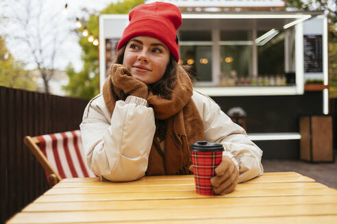 Woman in warm clothing looking away while sitting with hand on chin at sidewalk cafe - OYF00330