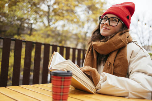 Smiling woman with book looking away while sitting at sidewalk cafe - OYF00333
