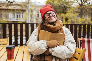 Woman in warm clothing embracing book while sitting at cafe - OYF00336