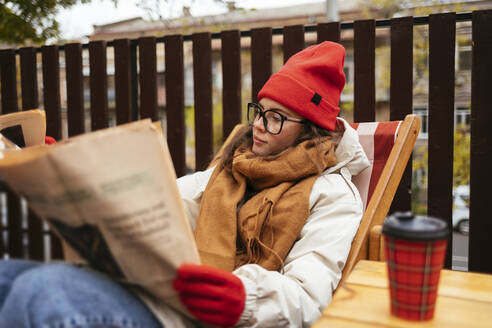 Young woman in warm clothing reading newspaper while relaxing on chair at cafe - OYF00339