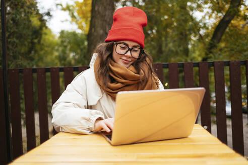 Smiling woman using laptop while sitting at sidewalk cafe - OYF00342