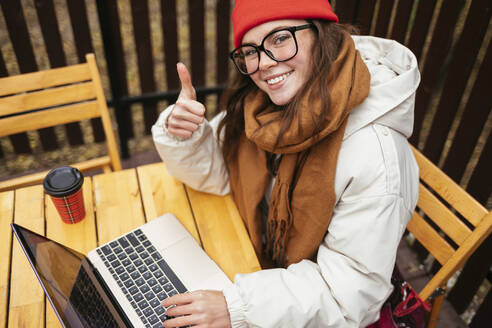 Young woman showing thumbs up while sitting with laptop at sidewalk cafe - OYF00345