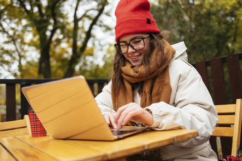 Woman wearing knit hat and scarf smiling while working on laptop at sidewalk cafe - OYF00348