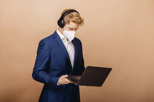 Businessman wearing suit and protective face mask using laptop while standing against beige background - DAWF01760