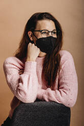 Woman wearing face mask looking away while standing by chair against beige background - DAWF01763