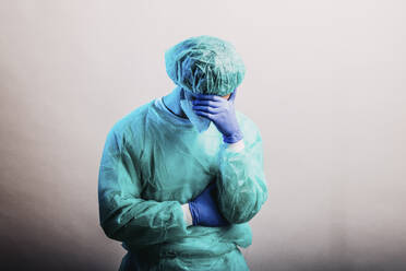 Male healthcare worker in protective suit and face mask standing with hand in hands against gray background - DAWF01766