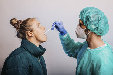 Expertise taking female patient throat exam while standing against gray background - DAWF01769
