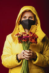 Woman wearing face mask and hooded shirt holding flower while standing against red background - DAWF01772