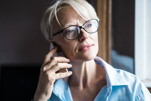 Businesswoman with eyeglasses looking away while talking on mobile phone in home office - MOEF03573
