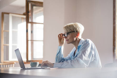 Businesswoman adjusting eyeglasses while working on laptop at desk in home - MOEF03579