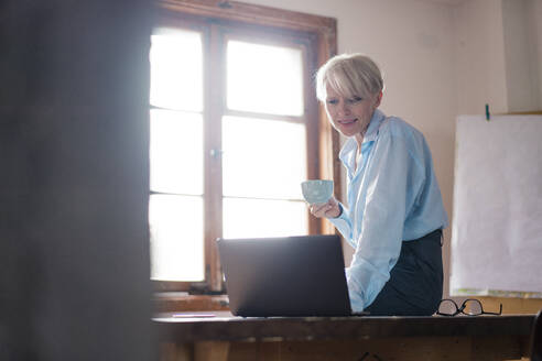 Smiling businesswoman holding coffee cup while using laptop on desk in home office - MOEF03582