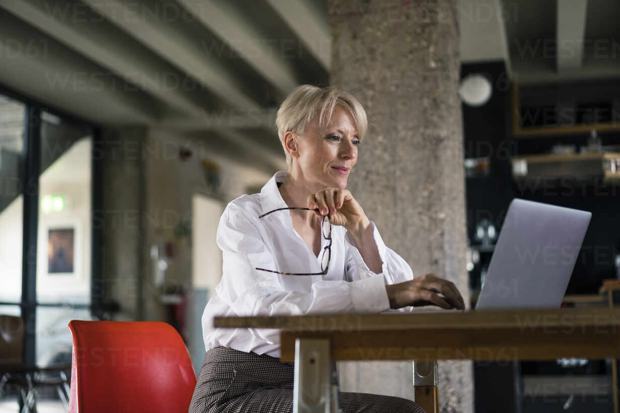 Smiling businesswoman holding eyeglasses while using laptop at desk by column at home office - MOEF03600 - Robijn Page/Westend61