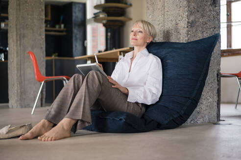 Businesswoman with digital tablet looking away while relaxing on floor chair at home - MOEF03603