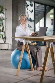 Smiling businesswoman working on laptop while sitting on fitness ball at desk in home office - MOEF03612