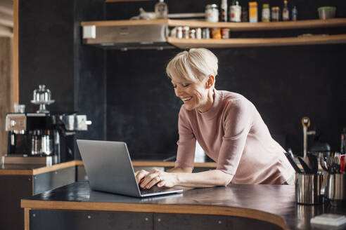 Happy businesswoman working on laptop at kitchen counter in home office - MOEF03630