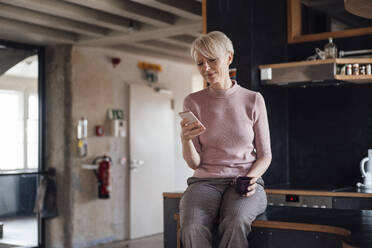 Smiling businesswoman with coffee cup using mobile phone while sitting on kitchen counter at home - MOEF03636