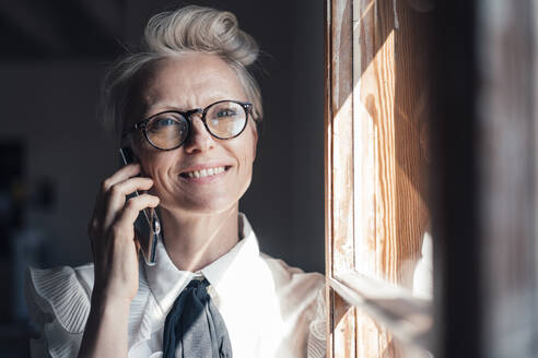 Smiling businesswoman with eyeglasses looking away while talking on smart phone at window in home office - MOEF03651
