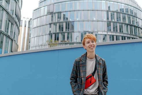 Smiling redhead man against building - OGF00888