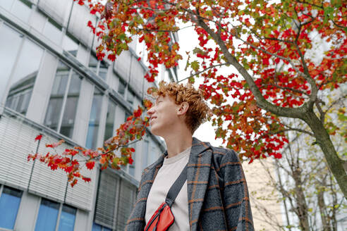 Redhead man looking away against tree during autumn - OGF00891