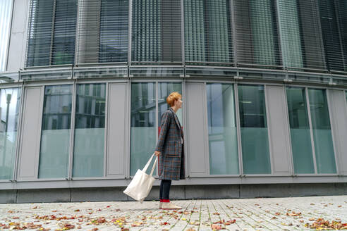 Man with tote bag standing by building on footpath - OGF00894