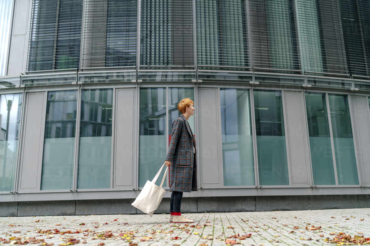 Man with tote bag standing by building on footpath - OGF00894 - Oxana Guryanova/Westend61