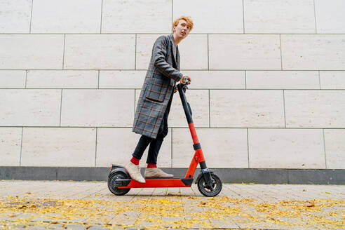 Man with electric push scooter on footpath by wall - OGF00900