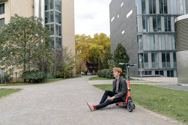 Man sitting on electric push scooter against building - OGF00903