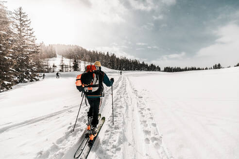 Active senior man skiing on snow covered land during vacation - DAWF01774