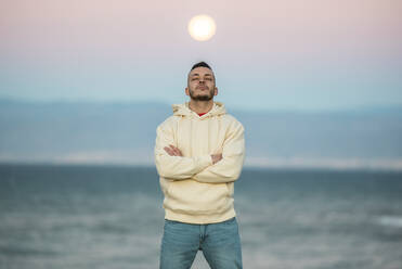 Mid adult man standing with eyes closed and arms crossed against moon - MIMFF00562