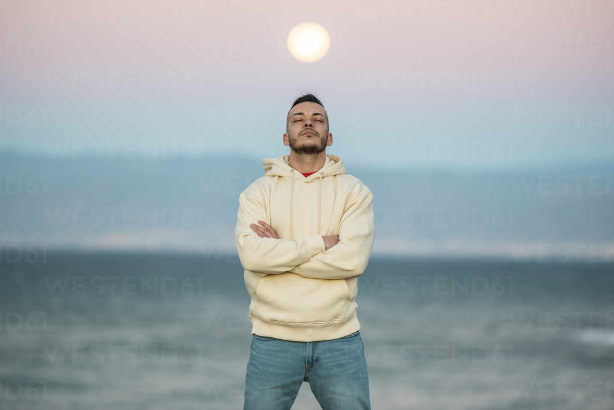 Mid adult man standing with eyes closed and arms crossed against moon - MIMFF00562 - Miguel Frias/Westend61