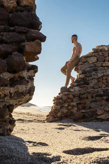 Shirtless man looking away while leaning on stone wall at beach - MIMFF00571