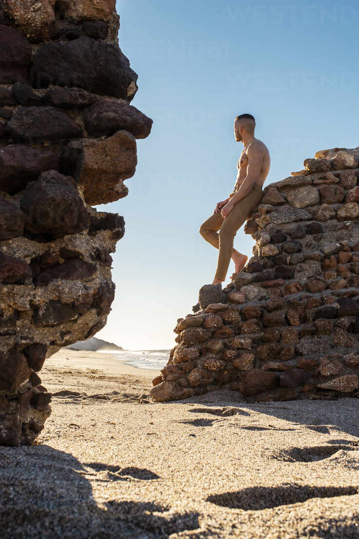 man on a stone wall next to the beach - spain, andalucia, almeria - MIMFF00571 - Miguel Frias/Westend61